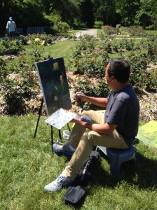 A plean air artist captures a yellow rose on canvas.