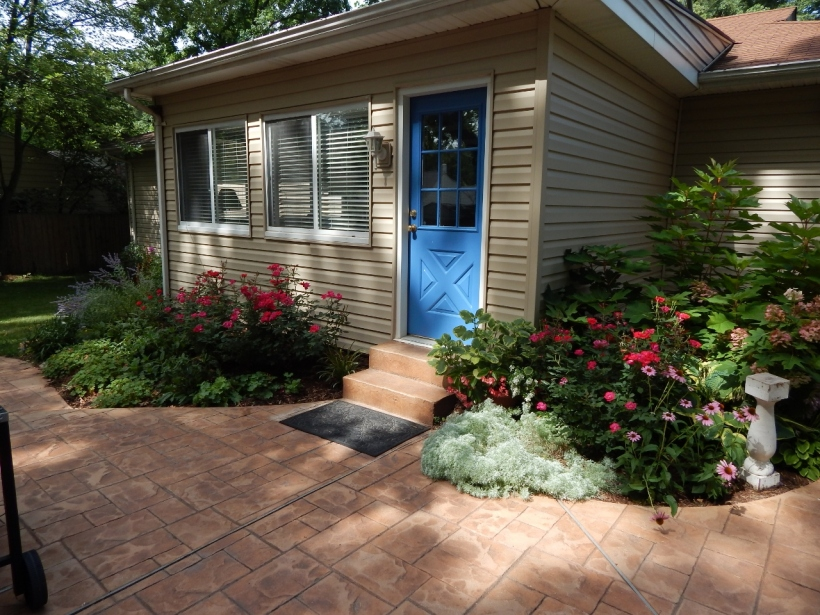 "My ""vision"" is to wrap gardens around the house. The blue door is the entry to the den, which faces east."