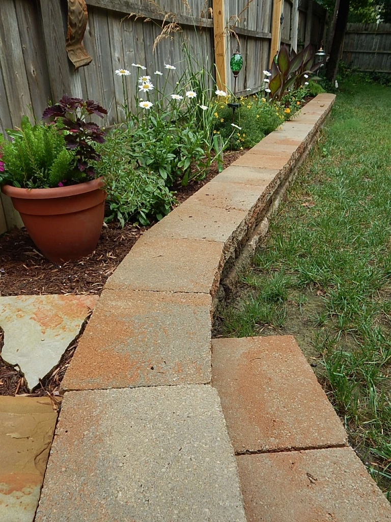 The addition of a step off of the raised area, makes stepping into the yard easier.